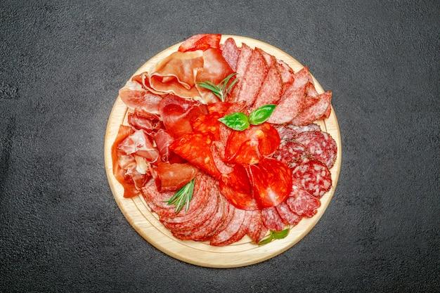 Assiette de viande froide avec saucisson salami et chorizo sur planche de bois