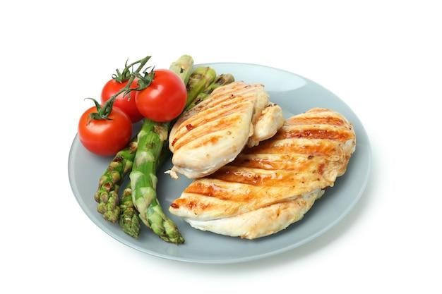 Assiette avec viande de poulet grillé, asperges et tomates isolé sur fond blanc