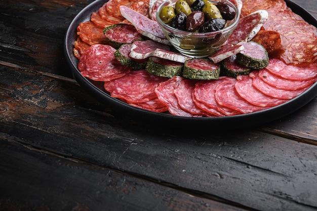 Assiette de viande séchée de tapas espagnoles traditionnelles. chorizo, salchichon, longaniza et fuet sur fond en bois foncé avec un espace pour le texte.