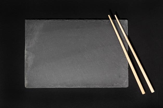 Assiette vide en ardoise noire et baguettes sur fond noir.