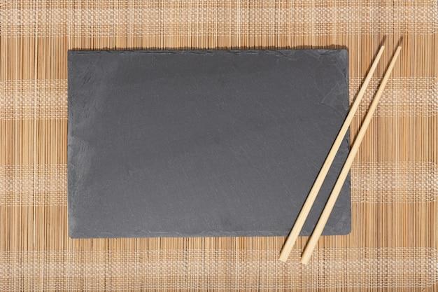 Assiette vide en ardoise noire et baguettes sur fond texturé en bambou.