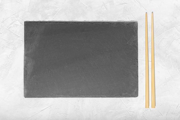 Assiette vide en ardoise noire et baguettes sur fond texturé blanc.