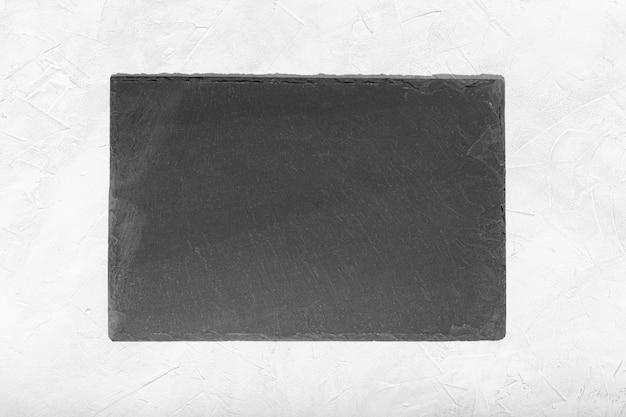 Assiette vide en ardoise noire isolé sur fond texturé blanc.