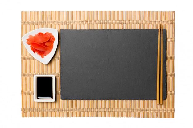 Assiette vide en ardoise noire rectangulaire avec des baguettes pour sushi, gingembre et sauce soja sur tapis en bambou jaune.