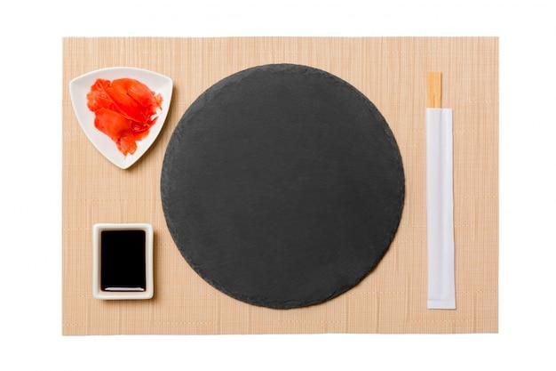 Assiette vide avec des baguettes pour sushi et sauce soja, gingembre sur fond de tapis de sushi brun. vue de dessus avec espace de copie pour votre conception