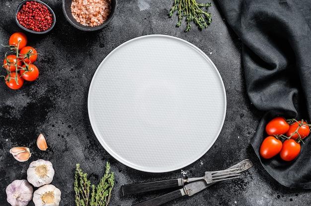 Assiette vide blanche au centre de légumes verts crus frais
