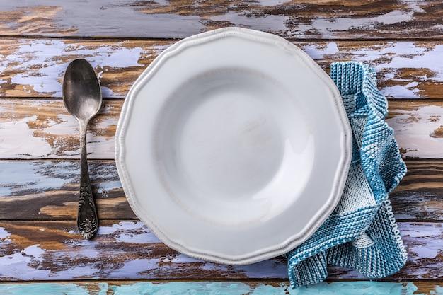 Assiette vide blanche sur une vieille table en bois, concept de fond bleu