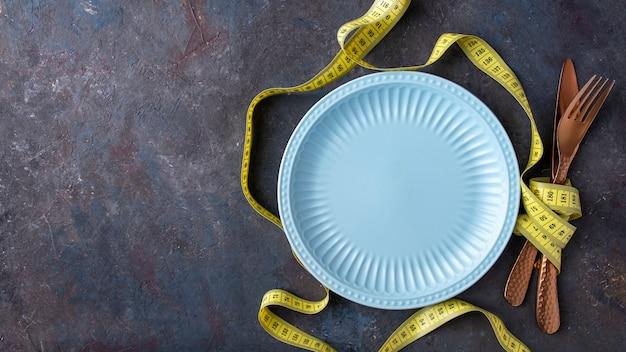 Assiette vide bleu avec couteau, fourchette et ruban à mesurer