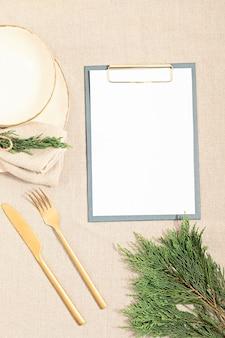 Assiette vide et branches de sapin sur nappe en lin dans des couleurs neutres naturelles. mise à plat, vue de dessus