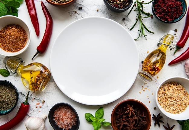 Assiette vide et cadre d'épices, d'herbes et de légumes sur un fond de marbre blanc. vue de dessus, pose à plat.