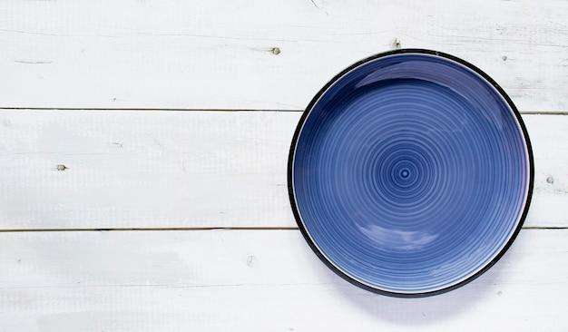 Assiette vide en céramique ronde bleu foncé placée sur le fond de texture noir et blanc de la table en bois, vue de dessus, espace de copie pour le menu d'un plat de restaurant.