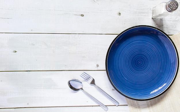 Assiette vide en céramique ronde bleu foncé placée sur la table, un fond de texture en béton noir et blanc a une bouteille de sel et une fourchette cuillère, vue de dessus, maquette pour un plat de restaurant.
