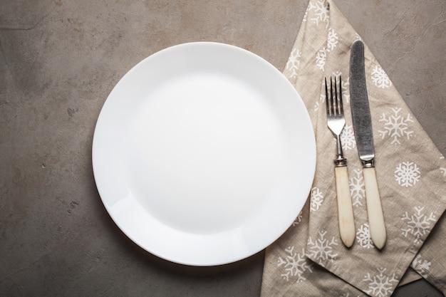 Assiette vide avec des couverts et une serviette beige avec des flocons de neige.
