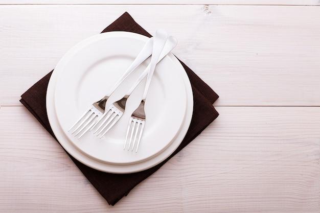 Assiette vide, couverts et serviette sur un bureau en bois