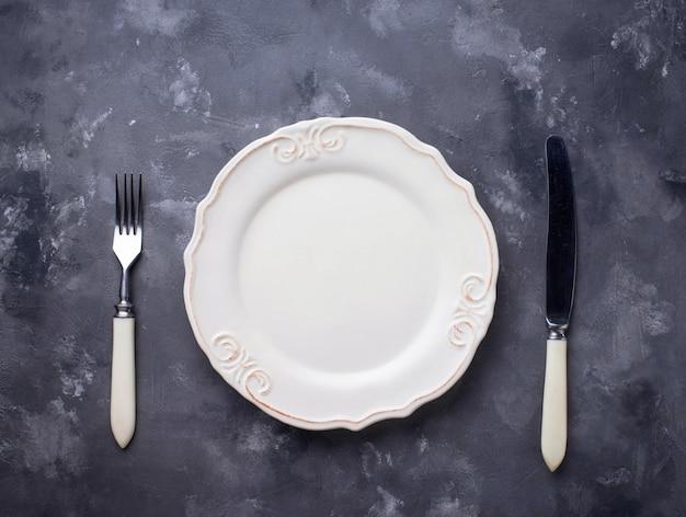 Assiette vide et couverts sur une table en béton