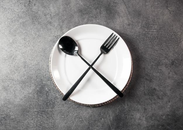Assiette vide cuillère fourchette et couteau sur table