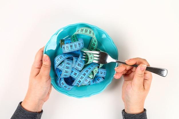 Assiette vide avec du ruban de mesure bleu