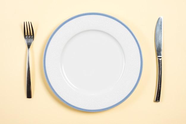 Une assiette vide entre la fourchette et le couteau à beurre sur fond beige