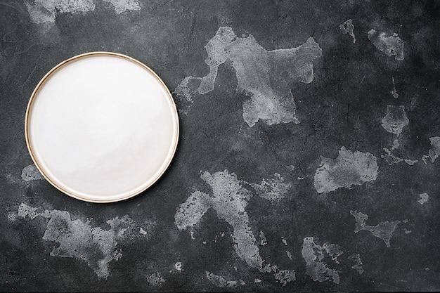 Assiette vide avec espace de copie pour le texte ou la nourriture avec espace de copie pour le texte ou la nourriture, vue de dessus à plat, sur fond de table en pierre noire noire