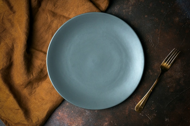 Assiette vide sur fond sombre. assiette en céramique grise vide avec un couteau et une fourchette pour la nourriture et le dîner sur un beau fond sombre.