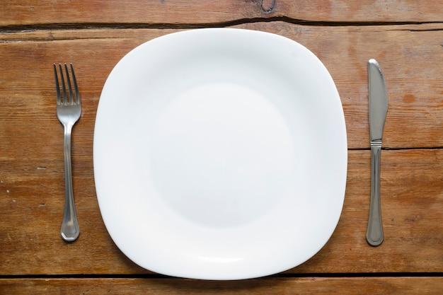 Assiette vide avec fourchette et couteau sur la table en bois vintage