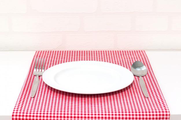 Assiette vide et fourchette cuillère sur la nappe à carreaux rouges et blancs