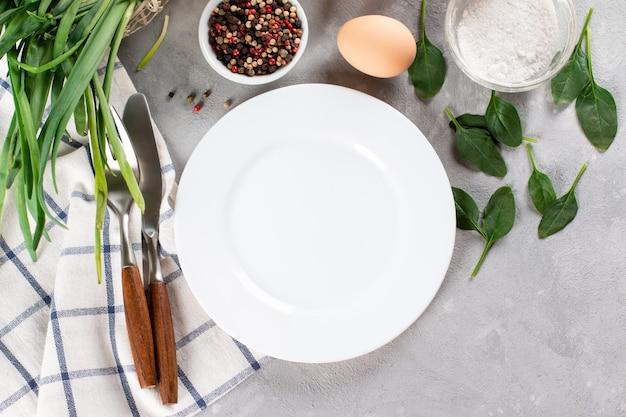 Assiette vide sur nappe sur table en bois sur fond bleu grunge