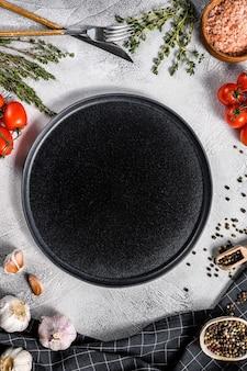 Assiette vide noire au centre de légumes verts crus frais