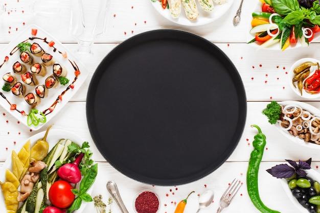 Assiette vide noire entourée de nourriture, vide