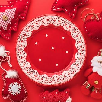 Assiette vide avec des ornements de noël et des jouets textiles sur une surface rouge