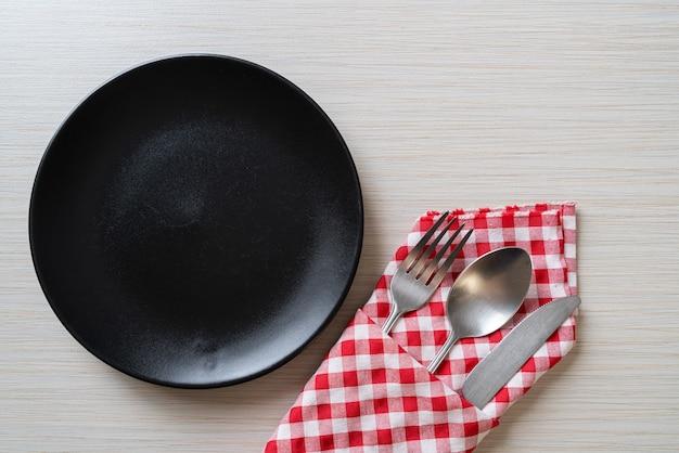 Assiette vide ou plat avec couteau, fourchette et cuillère sur table en bois