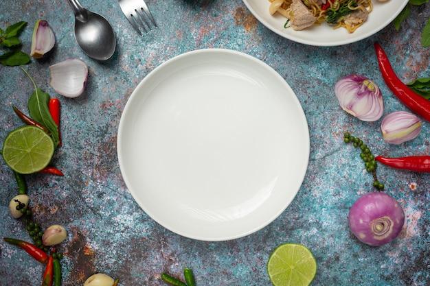 Une assiette vide ronde blanche parmi les ingrédients d'épices