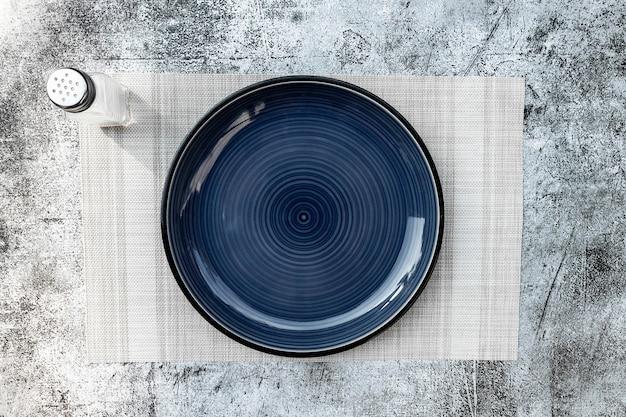 Assiette vide ronde bleu foncé placée sur la table fond de texture béton noir et blanc vue de dessus