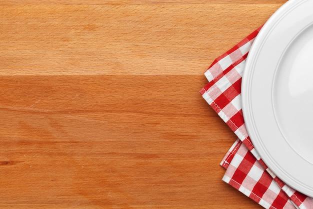 Assiette vide et une serviette sur la table en bois.