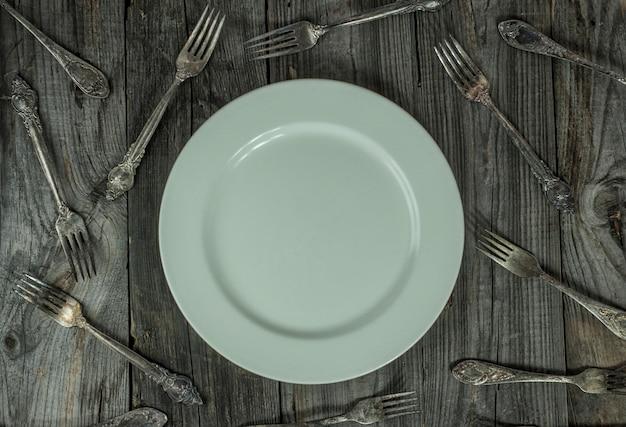 Assiette vide sur une surface en bois grise, autour de nombreuses fourchettes en fer