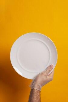 Assiette vide tenue par une main avec gant de protection