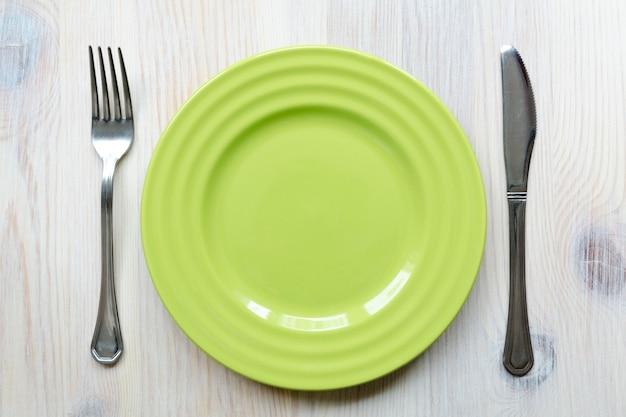 Assiette vide verte sur la table en bois vintage avec fourchette et couteau