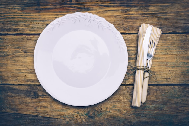 Assiette vide sur une vieille table en bois avec un couteau, une fourchette et une serviette