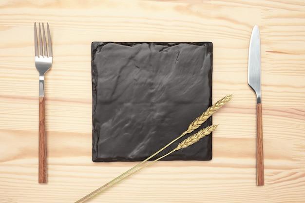 Assiette vierge et couverts sur table en bois, cartes et couverts sur table rustique. tableau de recettes orné d'épis dorés.