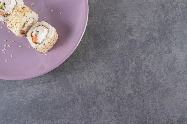 Assiette violette de rouleaux de sushi aux graines de sésame sur fond de pierre.