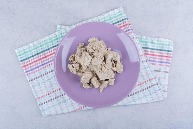 Assiette violette de savoureux halva de tournesol sur pierre.