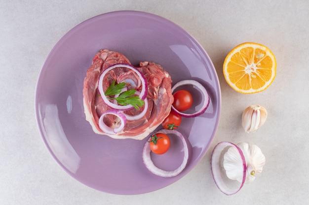 Assiette violette de viande d'agneau crue placée sur une table en pierre.