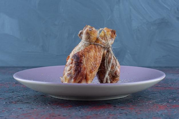 Une assiette violette avec de la viande de cuisses de poulet en corde.