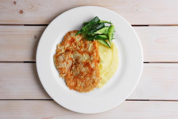 Assiette avec vue sur l'assiette avec du porc haché dans la chapelure et de la purée de pomme de terre décorée avec du concombre porc hachée dans de la panure et de la purée de pomme de terre décorée au concombre