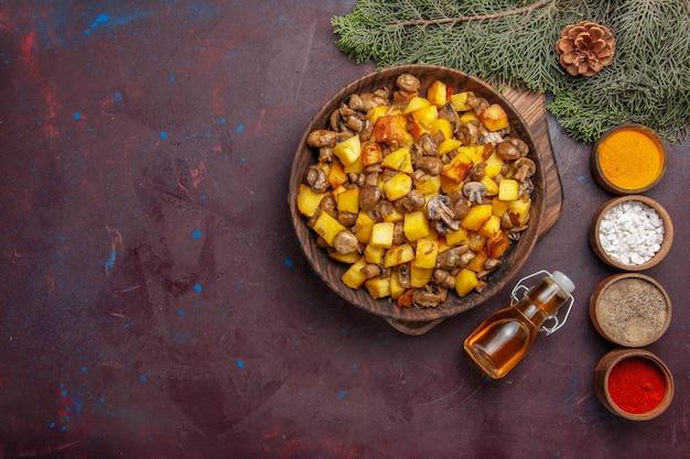 Assiette vue de dessus avec assiette de nourriture avec champignons frits et pommes de terre épices colorées et huile à côté de branches avec cônes