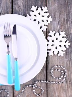 Assiettes blanches, fourchette, couteau et décoration d'arbre de noël sur table en bois