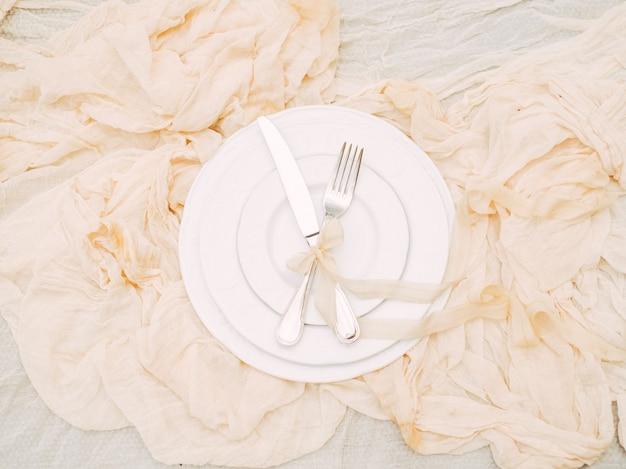 Assiettes blanches, fourchette, couteau et décoration