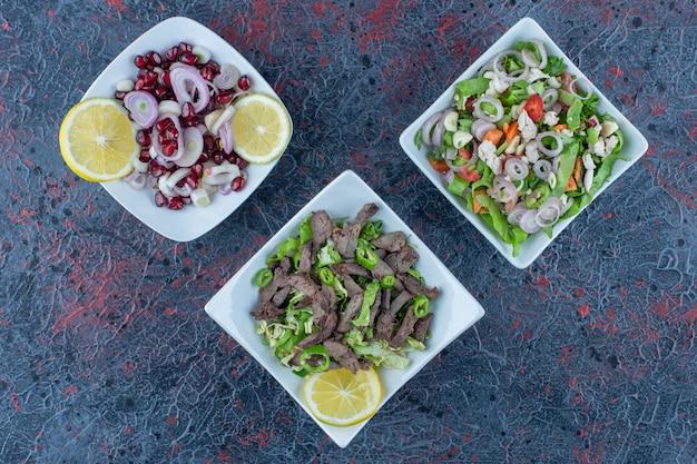 Assiettes blanches de salades de viande et de légumes.