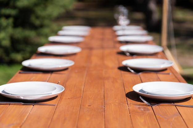 Des assiettes blanches sont placées sur une table en bois dans le parc sur une pelouse verte.