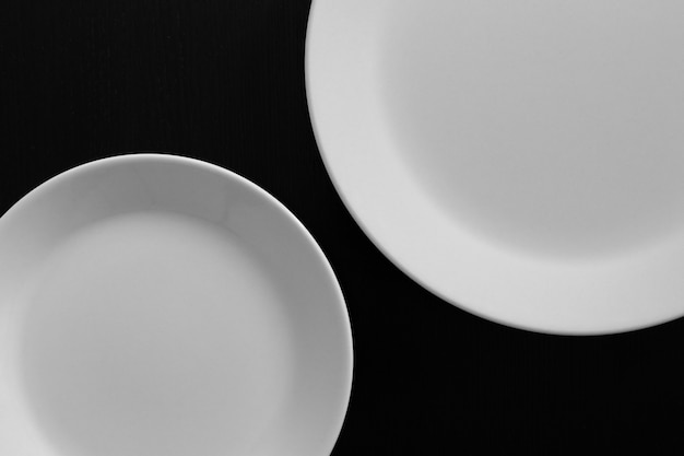 Assiettes blanches vides sur table en bois noir. ustensiles de cuisine se bouchent
